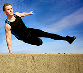 Young man jumping over wall on obstacle course