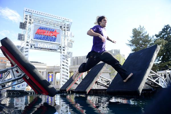 DENVER, CO - MAY 19: Course tester Christian Greene runs over an obstacle before the tryout for American Ninja Warrior Denver. (Photo by AAron Ontiveroz/The Denver Post)