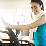 Attractive woman doing cardio exercise at gym